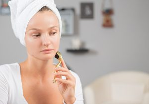 Woman using derma needle roller on her face