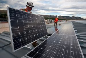 Two workers installing solar panels and 3 phase inverters