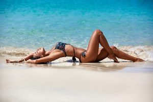 Sexy girl wearing a thong swimsuit bottoms while laying on the sand