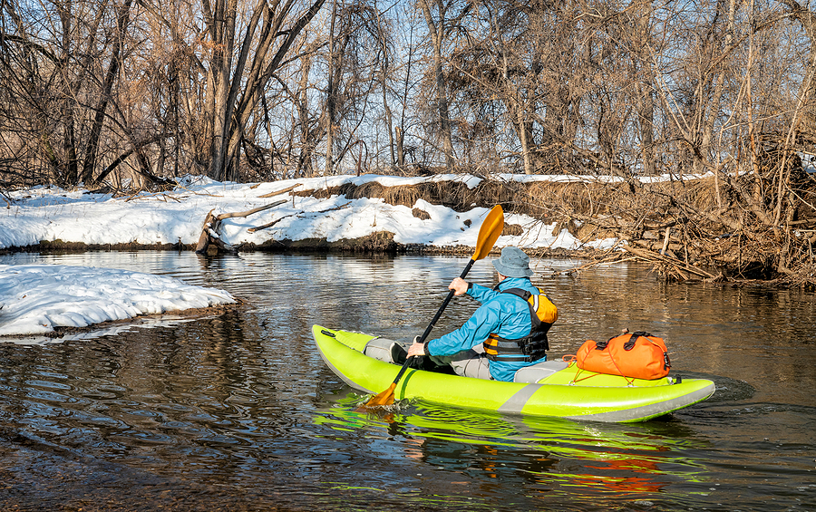Senior man paddling while riding the best inflatable kayaks
