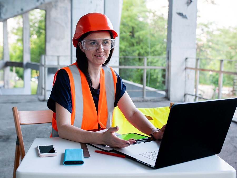 Construction manager using site diary in her laptop
